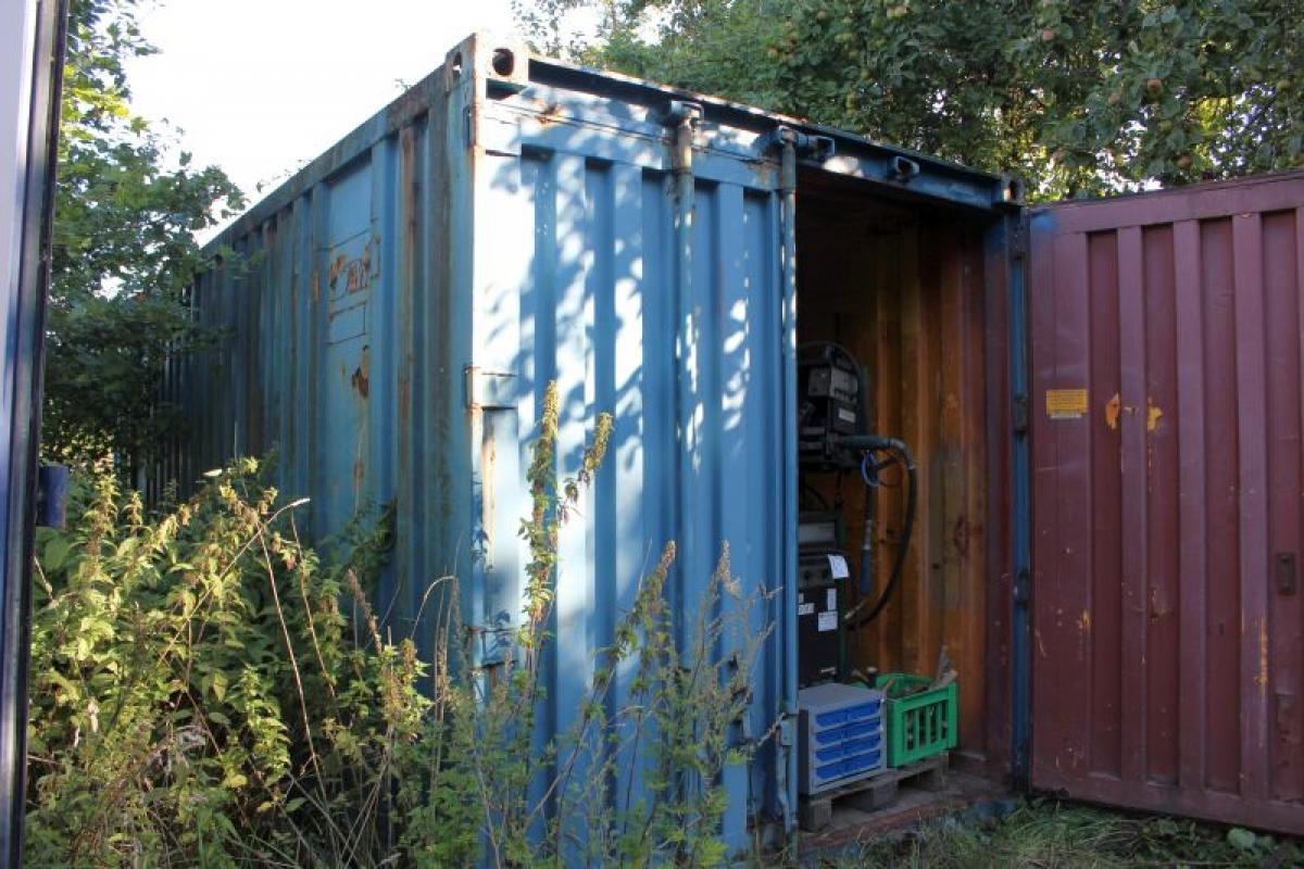 20 fu container mit einem loch im dach in der hinteren ecke b cherregal aus holz enth lt div. Black Bedroom Furniture Sets. Home Design Ideas